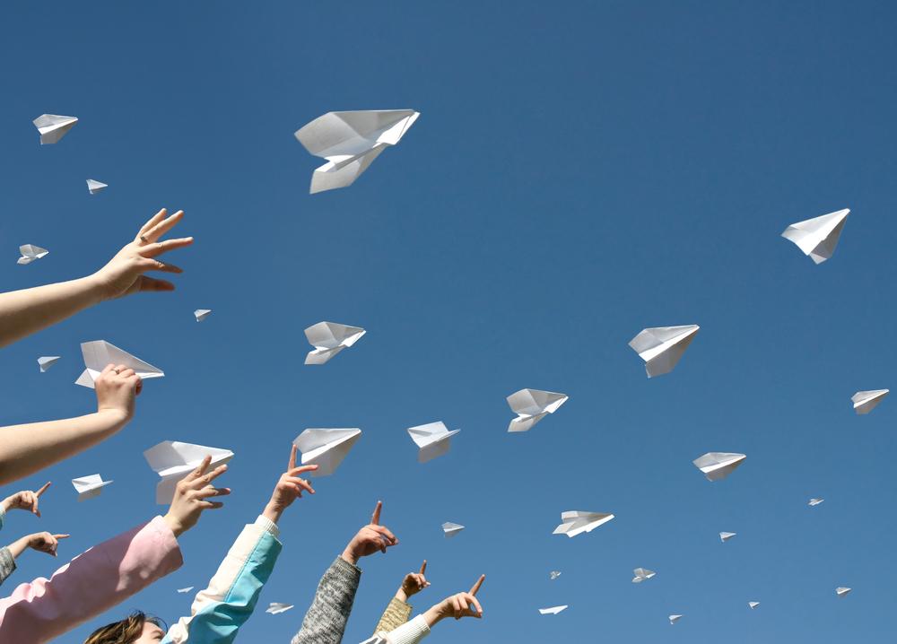 紙飛行機が一斉に飛ばされている様子
