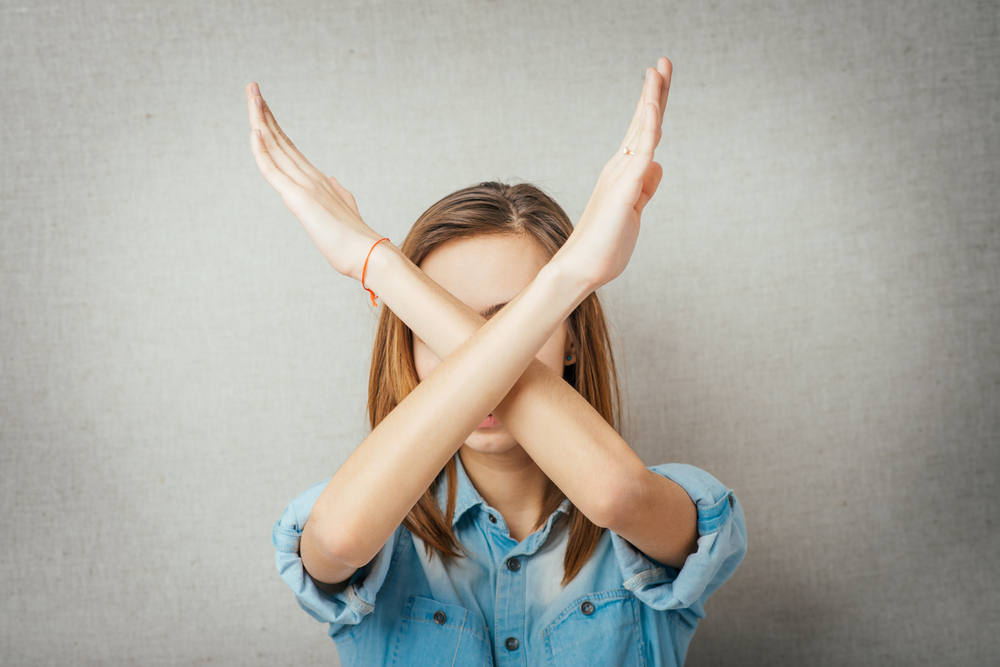 腕でバツ印をつくっている女性
