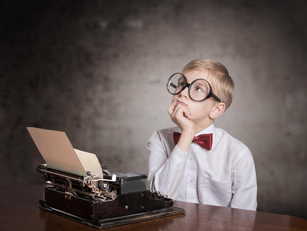 考えるメガネの少年とタイプライター