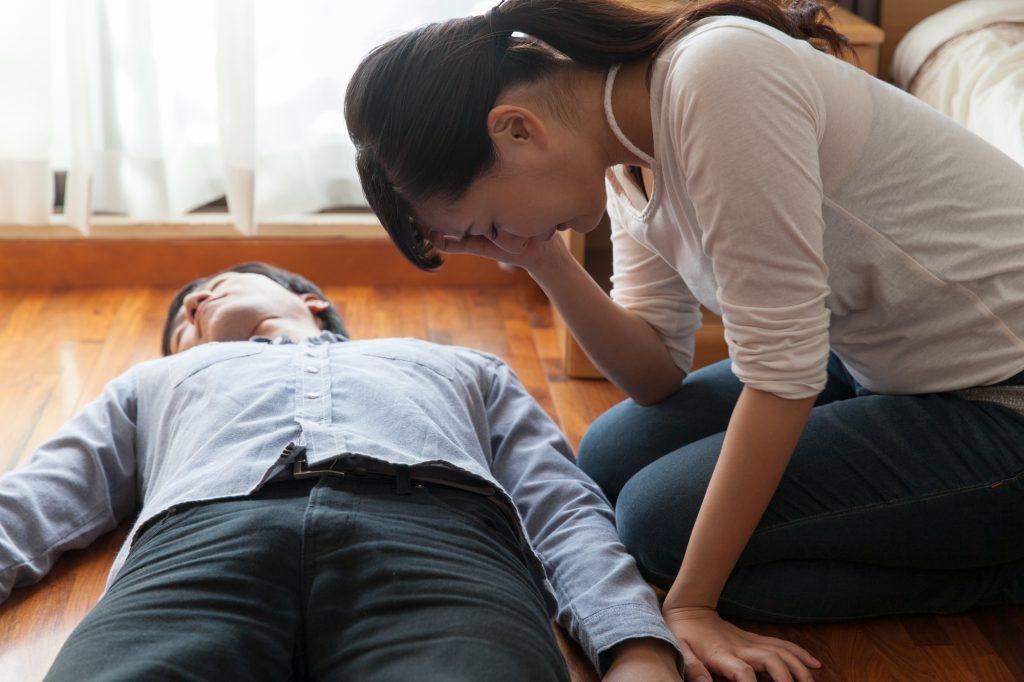 意識がなく横たわる男性と、公開している様子の女性